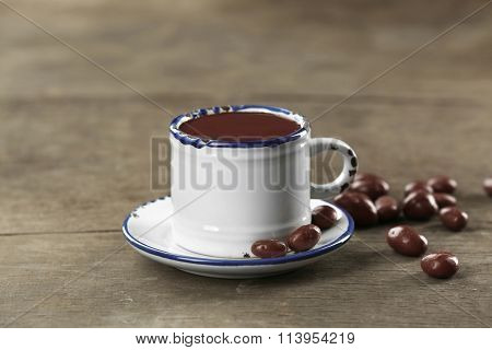 Cup of cacao with chocolate on wooden background