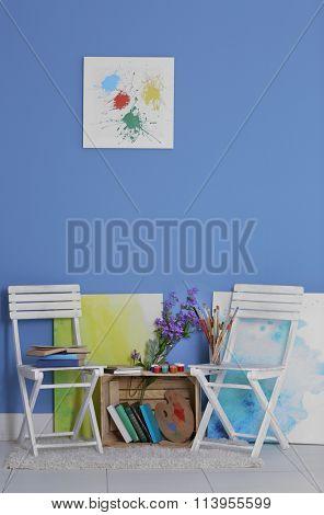 Room design with white chairs, bookcase, pictures and flowers over blue wall