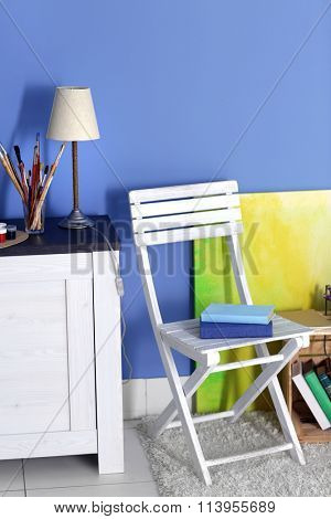 Room design with white chair, commode, picture, lamp over blue wall
