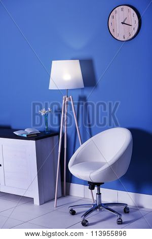 Modern living room with white armchair, commode and floor lamp near blue wall background