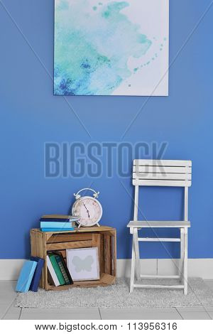 Room design with white chair, bookcase and picture over blue wall