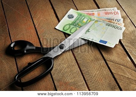 Scissors cut euro banknotes on wooden background