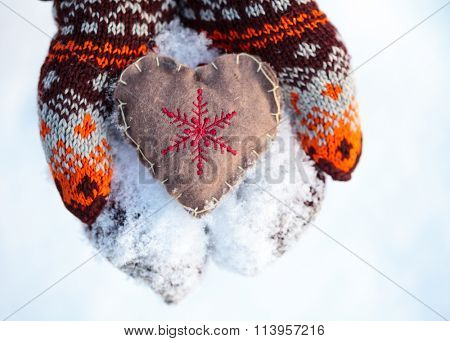 Woman wearing knitted mittens holding heart in cupped hands St. Valentine concept