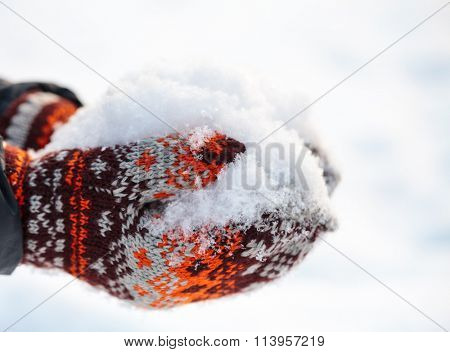 Woman wearing knitted woolen  mittens holding fresh snow in cupped hands