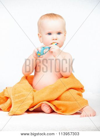Little baby girl wrapped in orange towel learning to brush teeth