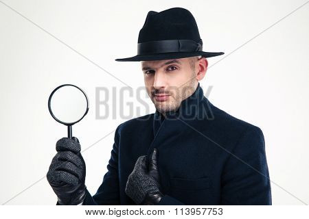 Portrait of serious handsome detective in black coat, hat and gloves holding magnifying glass over white background