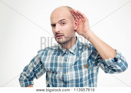 Curious handsome young man in plaid shirt overhearing rumors over white background
