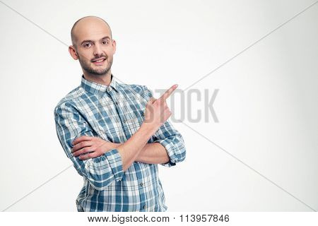 Cheerful attractive young man in plaid shirt standing and pointing away over white background