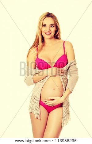 Pregnant woman in lingerie and cardigan