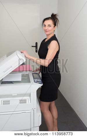 Pretty  Secretary Using  Photocopy Machine In Office