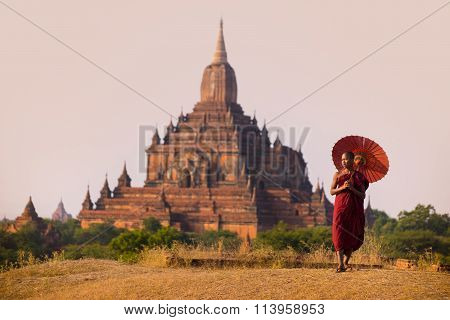 novice monk with red umbrella walking in front of Sulamani Pagodas. Bagan