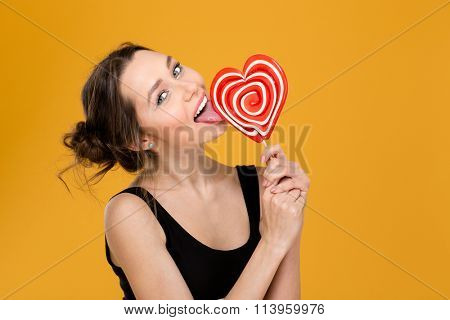 Lovely playful young woman licking sweet heart shaped lollipop over yellow background