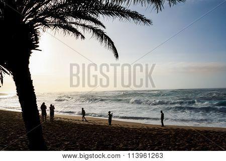 Tourists Taking Photos At Sunset On Sunset Beach