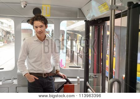 Young man in double decker tramway in Hong Kong
