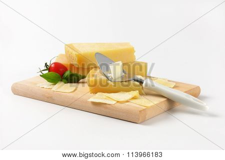 parmesan cheese and cheese knife on wooden cutting board