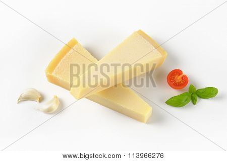 two wedges of fresh parmesan cheese and garnish on white background