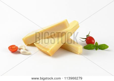 three wedges of fresh parmesan cheese and garnish on white background