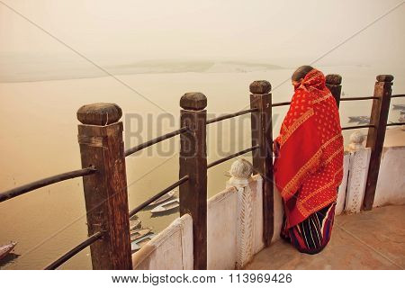 Lonely Woman Watching The Natural Landscape Behind Sacred Waters Of River Ganges In Indian City Vara