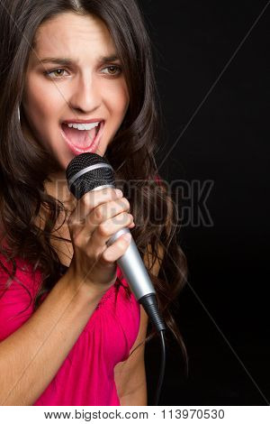 Beautiful girl singing with microphone