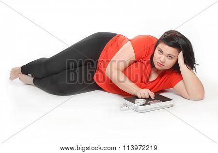 Overweight woman with measure tape and weighing machine. Picture on slimming theme.