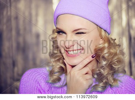 Gorgeous young blond woman wearing a purple outfit flirting with the camera smiling and winking with a playful expression, with copy space
