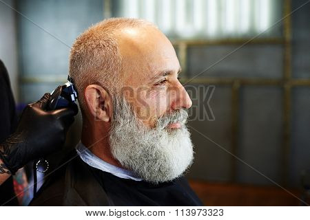 sideview of bearded senior man in barber shop