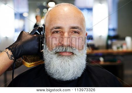portrait of bearded handsome senior man in barbershop. barber working with electric razor