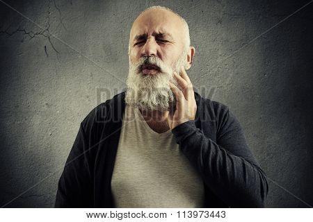portrait of winced senior man over dark background