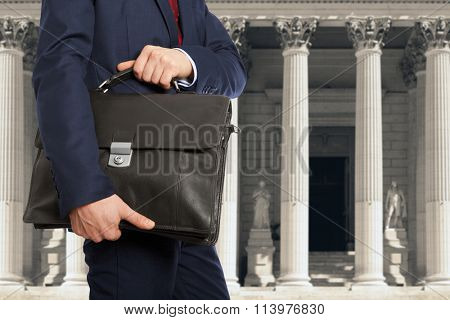 The lawyer with a briefcase is on against the courthouse