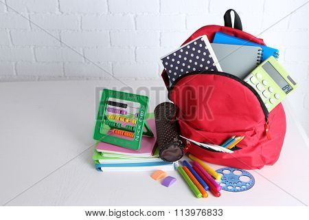 Backpack with school supplies on wooden table, on wall background