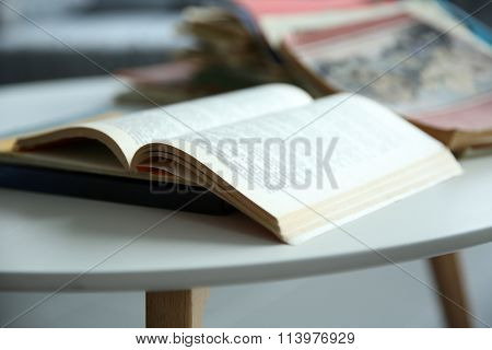 Pile of old books on white table, close up