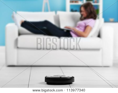 Cleaning concept - automatic robotic hoover clean the room while woman relaxing with laptop, close up