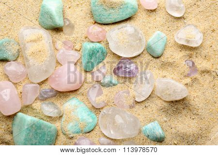 Semiprecious stones on sand background
