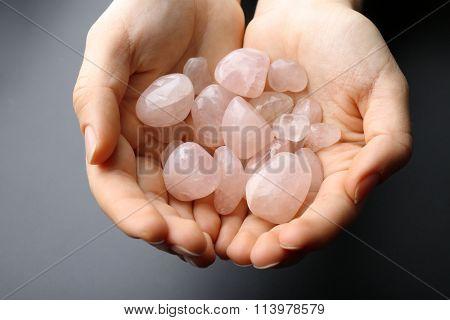 Woman holding semiprecious stones in her hands on dark grey background