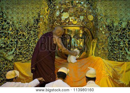 he senior monk wash Mahamuni Buddha image in ritual of the Buddha image face wash every morning.
