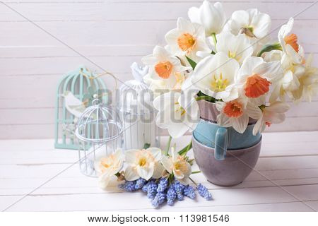 Fresh Spring Daffodils,  White Tulips Flowers, Muscaries Flowers And Candles    On White Wooden Plan