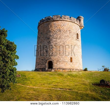 Round shaped, small, stone built, castle on plot of countryside land.