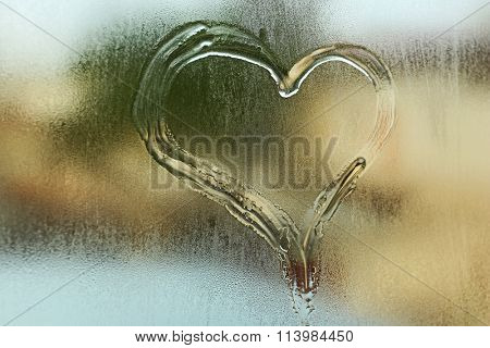 Heart drawn on the fogged glass window