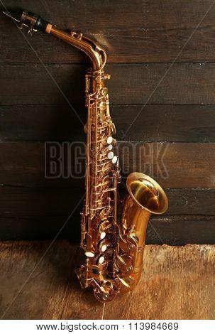 Beautiful golden saxophone on wooden background