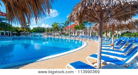 Warm sunshine, inviting pool scene and deck chairs. Holidays at a resort.