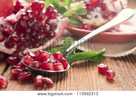 Pomegranate And Pomegranate Seeds In A Spoon