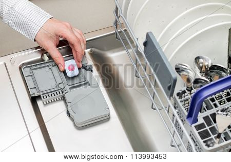 Man hand putting tablet in dishwasher detergent box