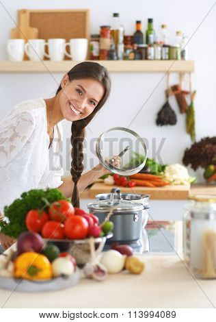 Young woman standing by the stove in the kitchen