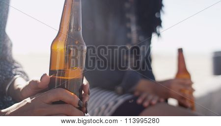 Close-up Of Woman Holding Beer Bottle With Friend In Background