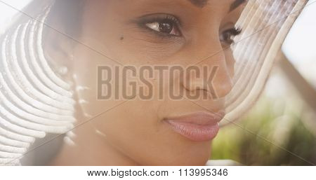 Close Up Backlit Shot Of Beautiful Black Woman Wearing Sunhat With Lens Flare