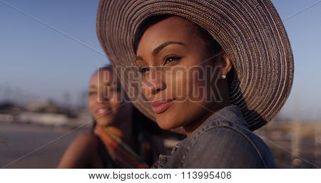 Black Women Best Friends Looking Out Over Ocean While Standing On Pier