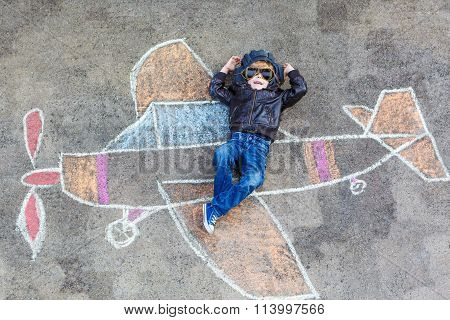 Little boy having fun with airplane picture drawing with chalk