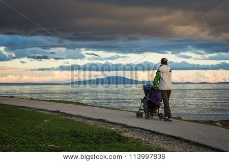 Mother with Baby Stroller Walking by the Sea