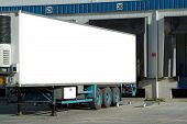 pic of tractor trailer  - trailer of truck sitting at a loading dock - JPG