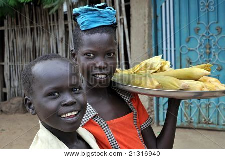 TEREKEKA – JUNE 11: Unidentified children selling cooked corn in Terekeka, South Sudan, on June 11, 2011. World Day Against Child Labour, launched by ILO, was observed on June 12, 2011.